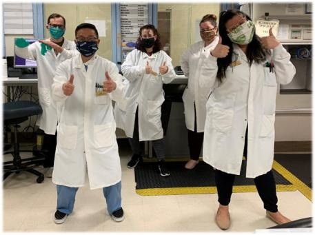 Five people in lab coats and face masks giving thumbs up to the camera