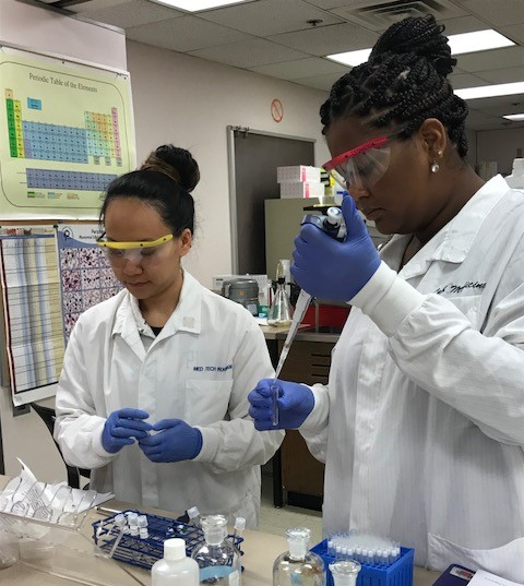 Two students in lab coats and goggles in a lab