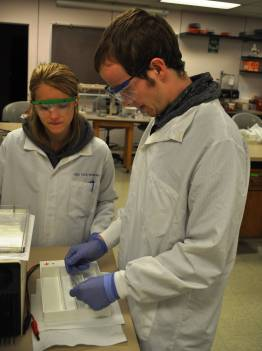 Two students in lab coats and goggles